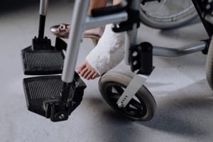 person with bondage foot while riding on wheelchair